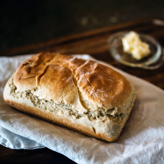 photo of bread with butter in the background